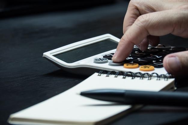 Chiuda sulla mano dell'uomo facendo uso del calcolatore sul fondo di legno dello scrittorio.