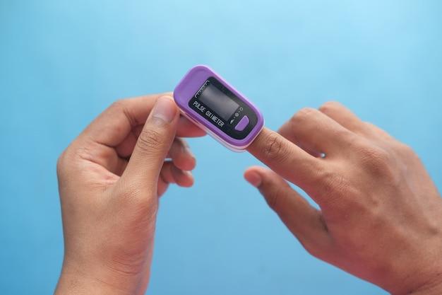 Primo piano della mano dell'uomo utilizzando il pulsossimetro
