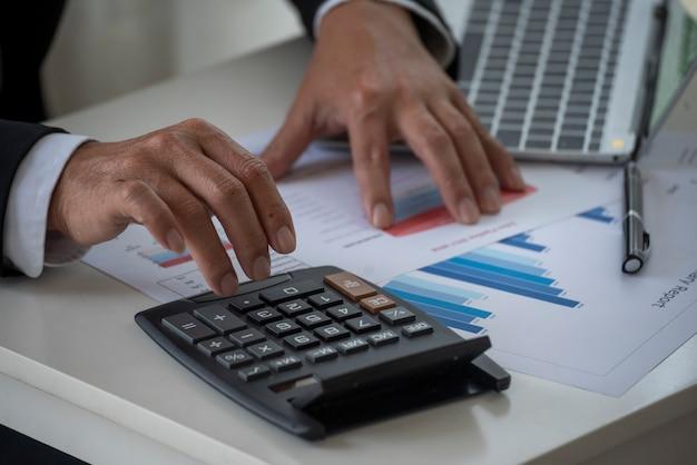 Primo piano le mani dell'uomo calcolano la contabilità di audit del grafico del grafico dei dati numerici sul rapporto aziendale