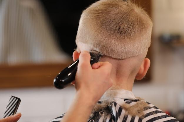 Primo piano delle mani dell'uomo che governano i capelli del ragazzo del bambino nel negozio di barbiere.