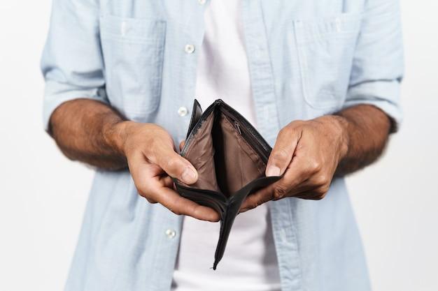 Primo piano delle mani dell'uomo che tengono e portafoglio vuoto su sfondo bianco. crisi finanziaria, fallimento, niente soldi, cattiva economia concetto.