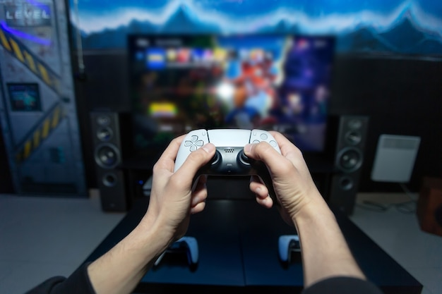 Primo piano delle mani dell'uomo che tengono i joystick wireless in primo piano. tv moderna con console.