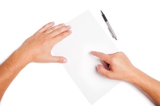 Mani dell'uomo del primo piano che indicano sullo spazio in bianco bianco con la penna isolata