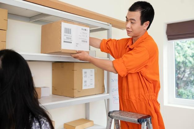 Chiuda in sull'uomo che aiuta la donna a raggiungere la scatola di consegna dallo scaffale