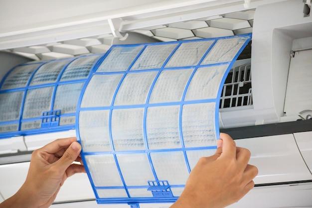 Primo piano sul filtro del condizionatore d'aria della stretta dell'uomo