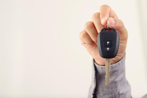 Uomo del primo piano che tiene le chiavi della macchina isolato su sfondo bianco