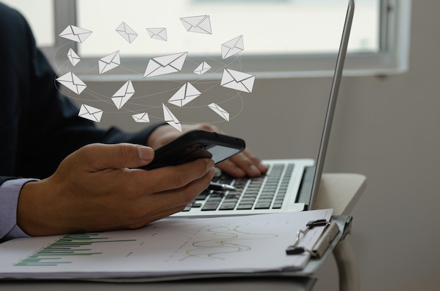 Uomo del primo piano che tiene un telefono cellulare un messaggio di posta elettronica dell'icona. attività di marketing che invia informazioni ai clienti o effettua l'hacking di transazioni online. tecnologia di concetto di affari.