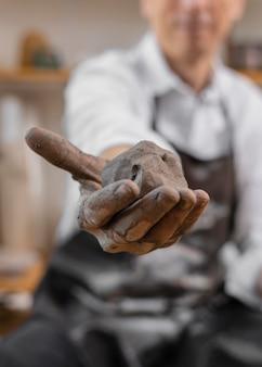 Uomo del primo piano che tiene argilla