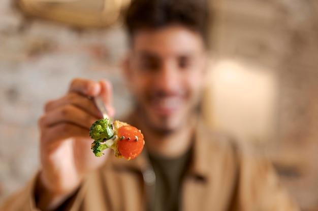 Chiuda sulla forcella della holding dell'uomo con il cibo
