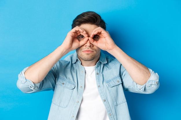 Primo piano dell'uomo che tiene le mani sugli occhi, guardando attraverso il binocolo con la faccia seria, in piedi sopra la parete blu