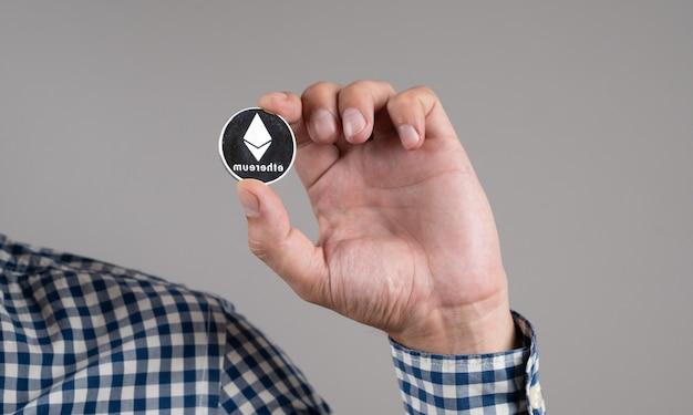 Close up uomo con moneta d'argento di ethereum. denaro digitale all'interno della rete blockchain.