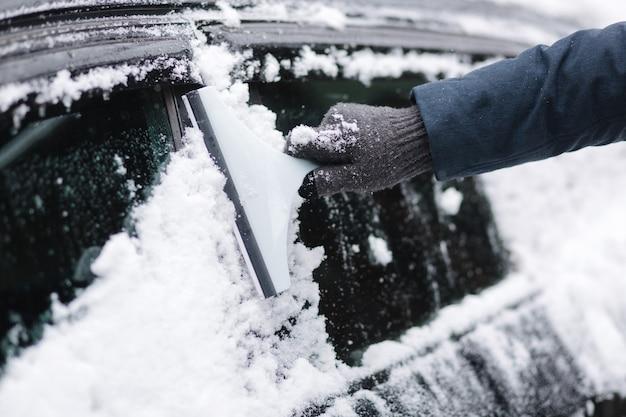 Primo piano dell'uomo sta pulendo il finestrino nevoso su una macchina con raschietto da neve concentrati sul raschietto. freddo