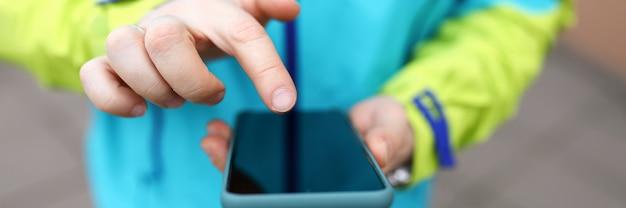 Il primo piano in giacca fa clic sul telefono del touch screen