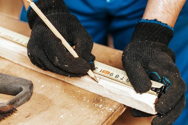 Primo piano l'uomo misura una tavola di legno e segna con la matita i punti necessari per le fette