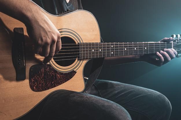 Primo piano di un uomo che suona una chitarra acustica al buio con illuminazione del palco.