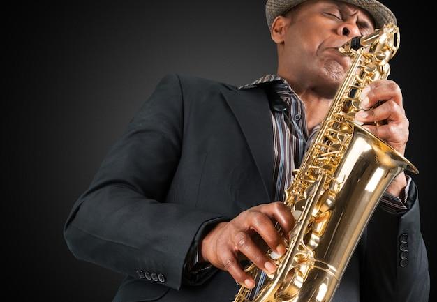 Uomo del primo piano che suona il sassofono sullo sfondo