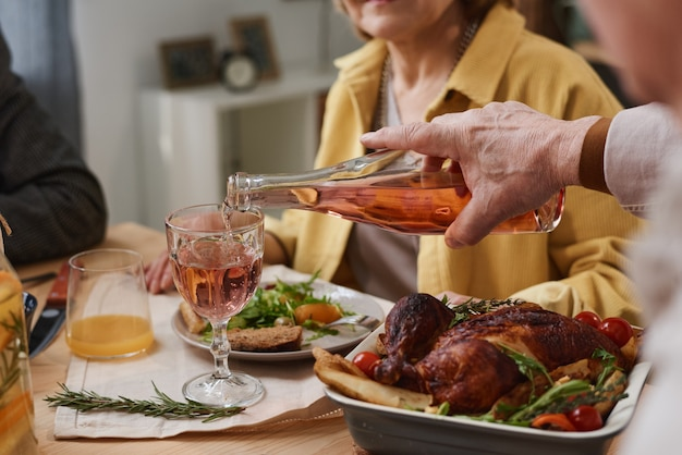 Primo piano dell'uomo che versa il vino nel bicchiere dalla bottiglia mentre cena con i suoi amici