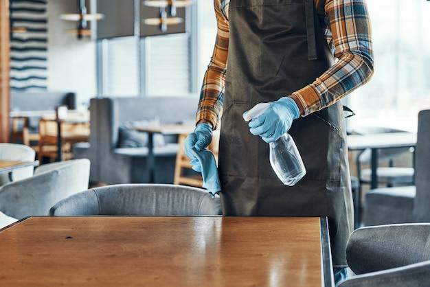 Primo piano di un uomo in guanti protettivi che pulisce il tavolo per i clienti mentre prepara il ristorante per l'apertura durante la pandemia