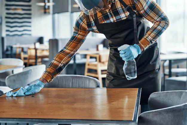 Primo piano di un uomo in guanti protettivi che pulisce il tavolo nel ristorante
