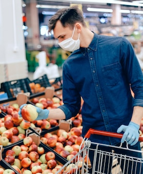 Avvicinamento. uomo in una maschera protettiva quando si selezionano le mele al supermercato. il concetto di assistenza sanitaria.