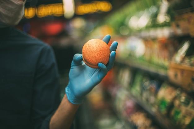 Avvicinamento. uomo in una maschera protettiva quando si selezionano le arance al supermercato. igiene e assistenza sanitaria