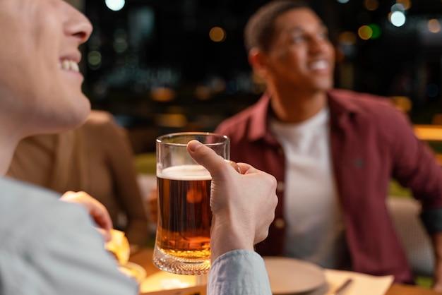 Uomo del primo piano al pub con la birra