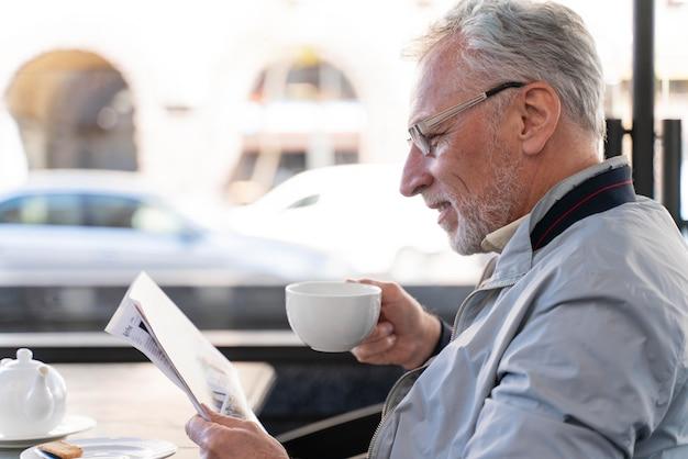 Primo piano uomo che legge il giornale