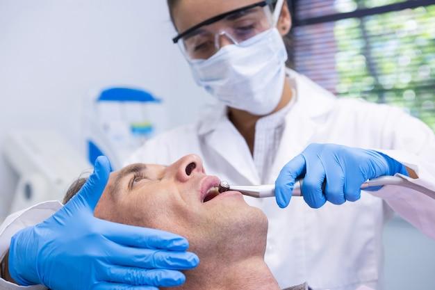 Chiuda in su dell'uomo che riceve il trattamento dentale dal dentista