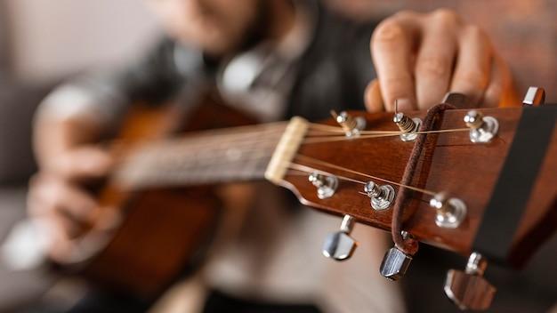 Uomo del primo piano che restringe la chitarra Foto Premium