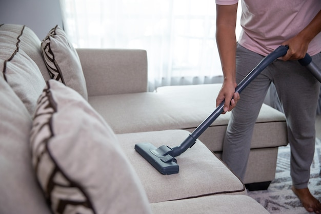 Chiuda in su del lettino per la pulizia della mano d'uomo utilizzando l'aspirapolvere a casa
