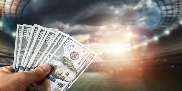 Primo piano della mano di un uomo che tiene i dollari usa sullo sfondo dello stadio. il concetto di scommesse sportive, realizzare un profitto dalle scommesse, dal gioco d'azzardo. football americano.