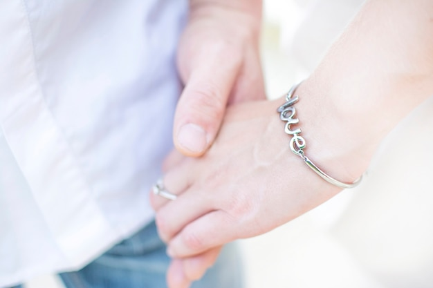 Primo piano della mano di un uomo che tiene la mano di una donna in un braccialetto con la scritta amore