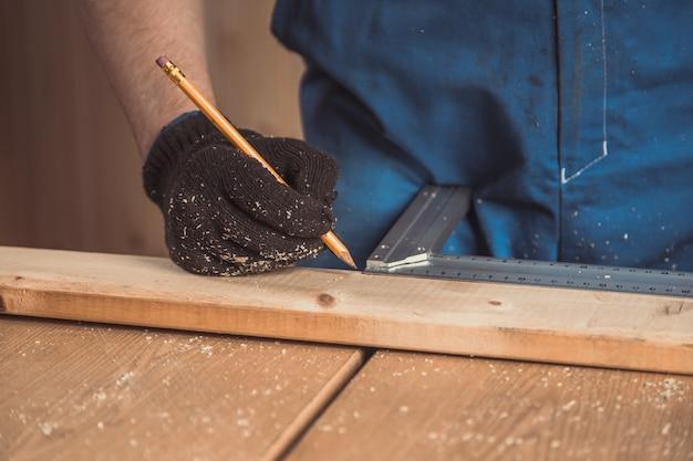 Primo piano della mano dell'uomo fa un segno su una tavola di legno