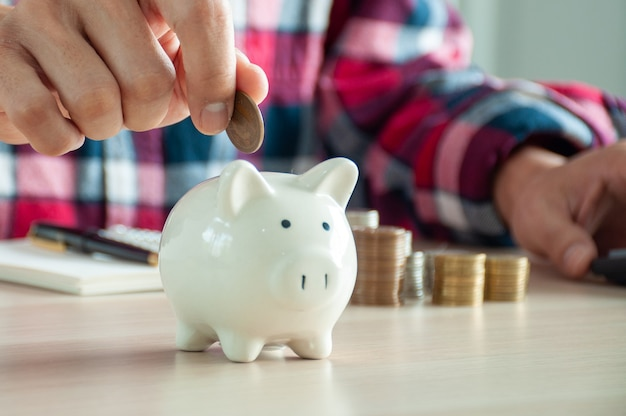 Primo piano della mano di un uomo che mette soldi in un salvadanaio per risparmiare dopo aver calcolato i costi. concetti di risparmio di denaro, finanziario, contabile