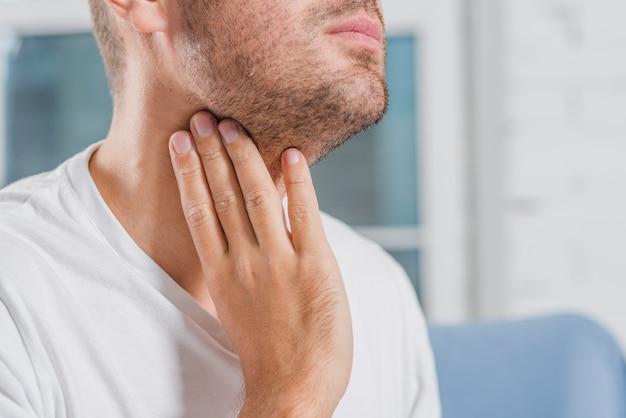 Primo piano della mano di un uomo che tocca la sua gola