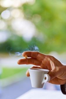 Chiuda sulla mano dell'uomo con la tazza di caffè nero e una sigaretta