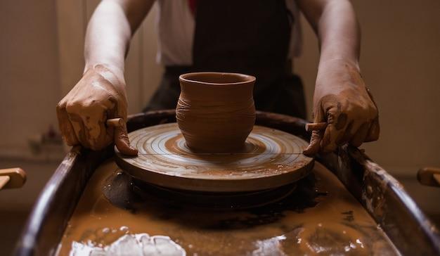 Primo piano delle mani di un uomo che tagliano una tazza di argilla con un filo su un telaio in una stanza