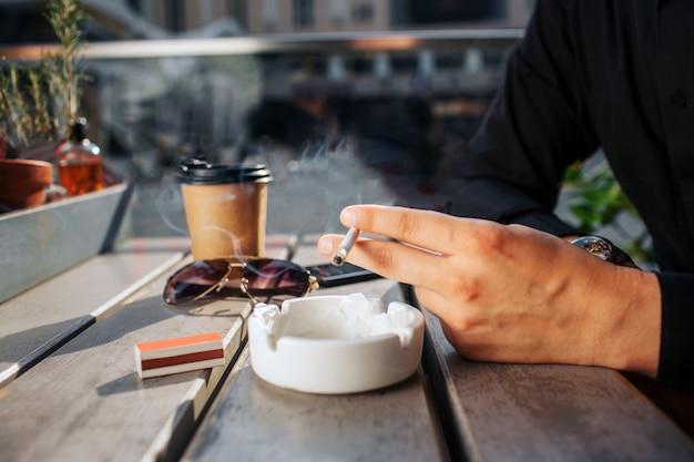 Chiuda in su delle mani dell'uomo tenere in mano la sigaretta. lo ha sopra il piatto bianco. ci sono bicchieri e bicchieri di bibite sul talbe. fuori c'è il sole. Foto Premium