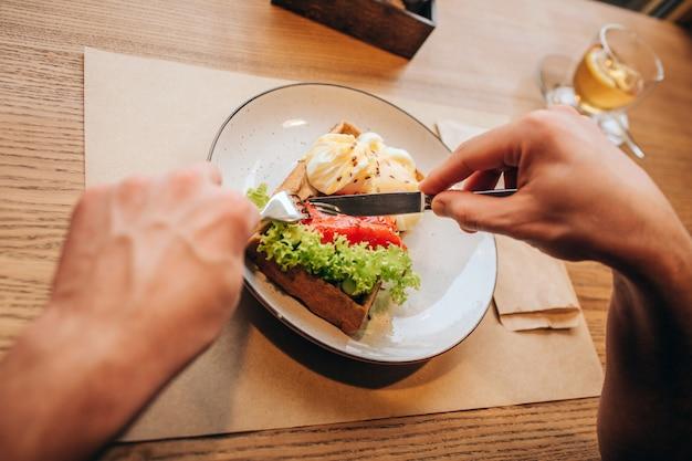 Chiuda in su delle mani dell'uomo tenendo la forchetta e il coltello e tagliando il piatto in due pezzi. c'è una tazza di tè sul lato destro del pasto.