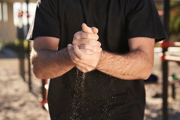 Primo piano delle mani di un uomo che mette il magnesio sulle sue mani, preparandosi a fare esercizi con bilanciere. con la sabbia tra le mani.