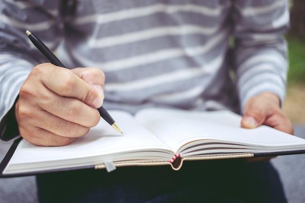 Chiuda in su delle mani dell'uomo scrivendo nel blocco note a spirale posto sul desktop in legno con vari oggetti