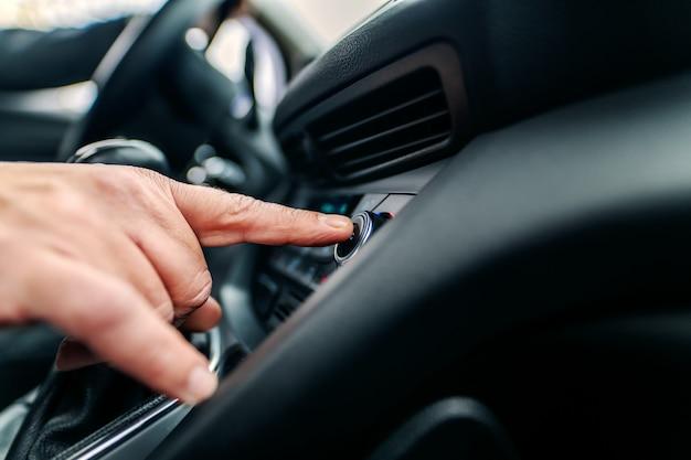 Chiuda su dell'uomo che cerca la buona stazione radio mentre si siedono in automobile.