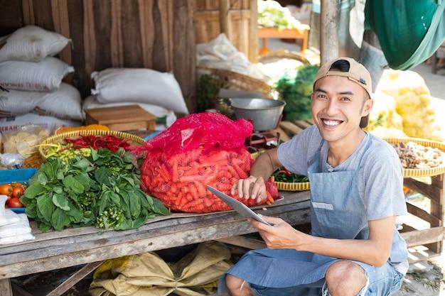 Chiuda in su dell'uomo che vende la bancarella di verdure sorridendo mentre si utilizza il tablet pc sullo sfondo della bancarella di verdure
