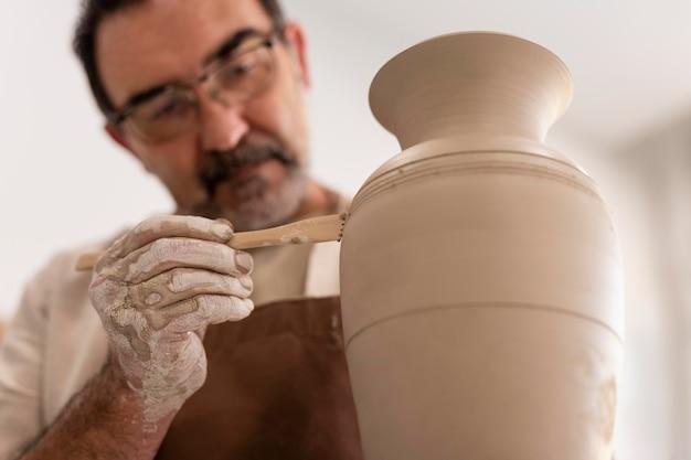 Close up uomo che modella vaso con strumento