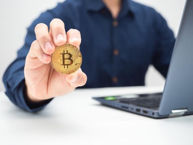 Uomo ravvicinato che mostra bitcoin dorato sul tavolo con un colpo di ritaglio del laptop