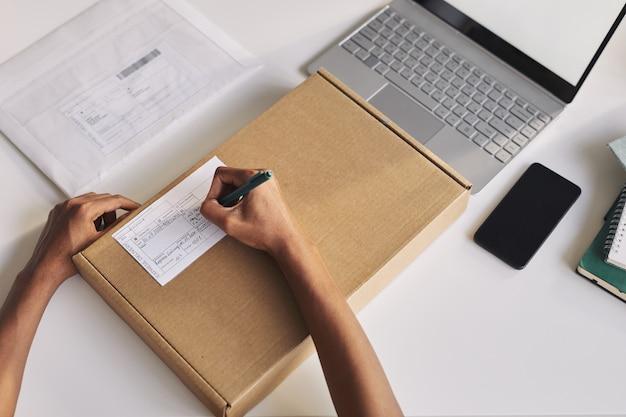 Primo piano dell'uomo seduto al tavolo davanti al laptop e compilando il modulo sul pacco che scrive il suo indirizzo