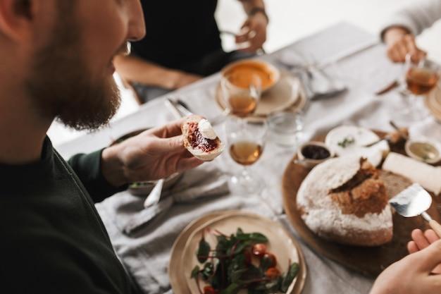 Chiuda sull'uomo seduto al tavolo che tiene fetta di pane con marmellata e formaggio in mano a pranzo in un accogliente caffè
