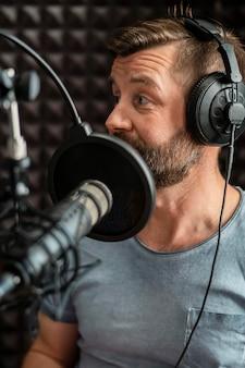 Uomo del primo piano che parla alla radio