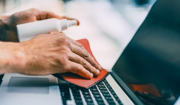 Avvicinamento. uomo che spruzza spray sulla superficie di un computer portatile. concetto di tutela della salute
