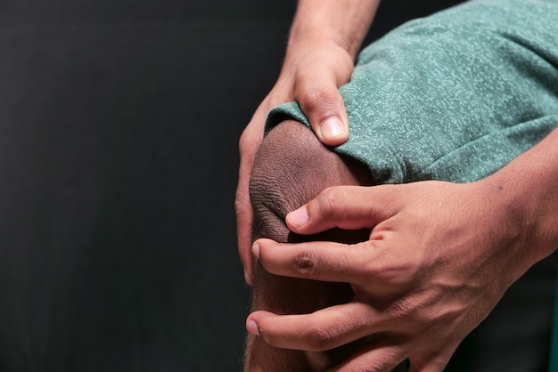 Primo piano sull'uomo che soffre di dolore alle articolazioni del ginocchio isolato in nero